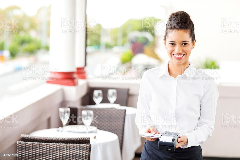 Waitress With Credit Card And Reader In Restaurant royalty-free stock photo
