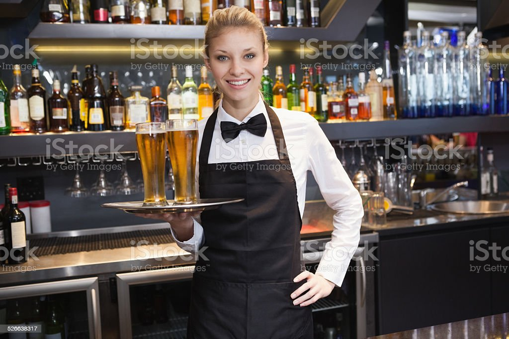 Waitress with hand on hip holding a tray of champagne stock photo