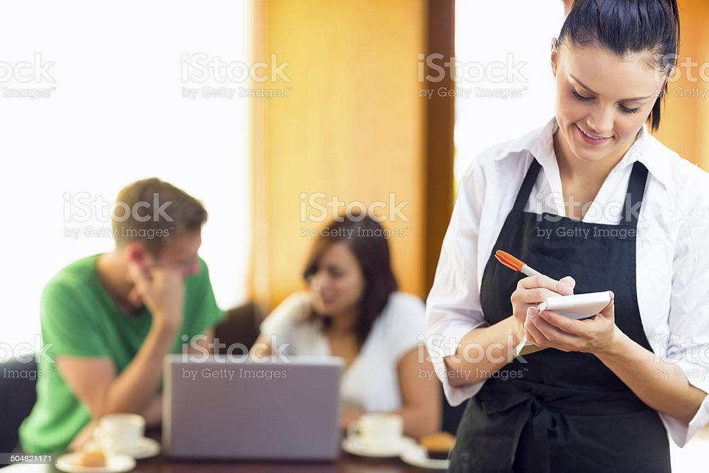 Waitress writing an order with students using laptop at  coffee stock photo