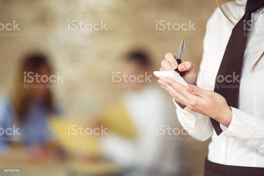 Waitress Writing In Order Pad At Restaurant. stock photo