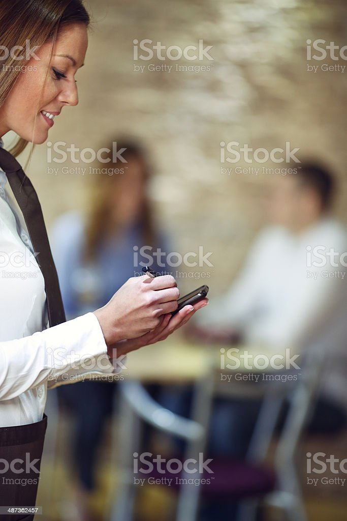 Waitress Writing In Order Smart Pad At Restaurant. stock photo