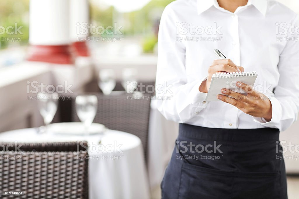 Waitress Writing On Order Pad In Restaurant stock photo