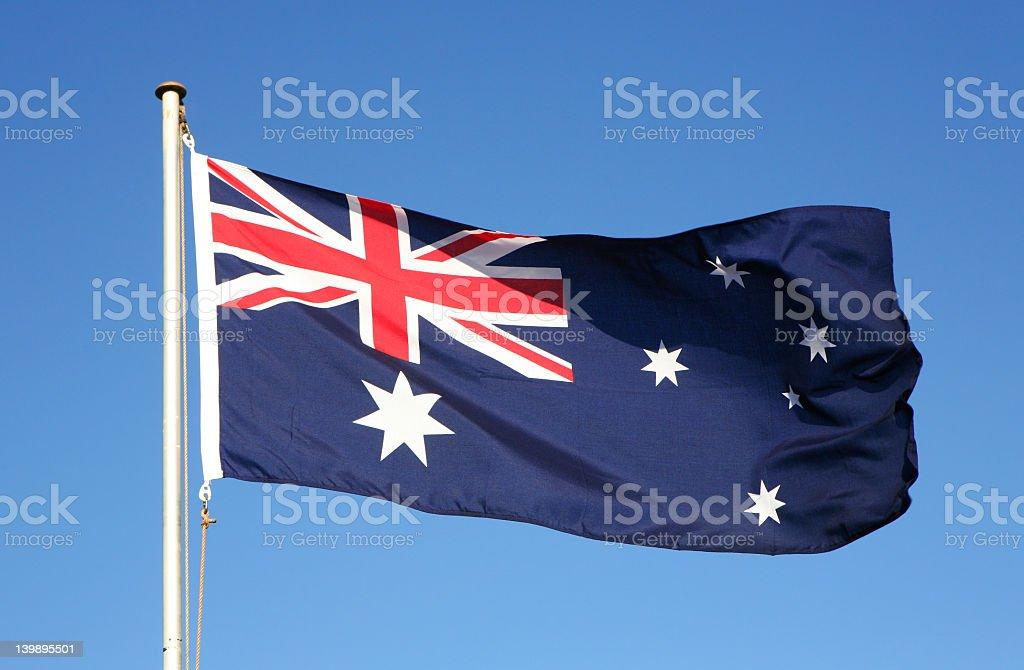 Waiving Australian flag on blue background stock photo