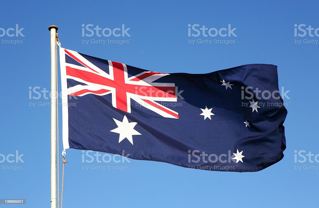 Waiving Australian flag on blue background stock photo