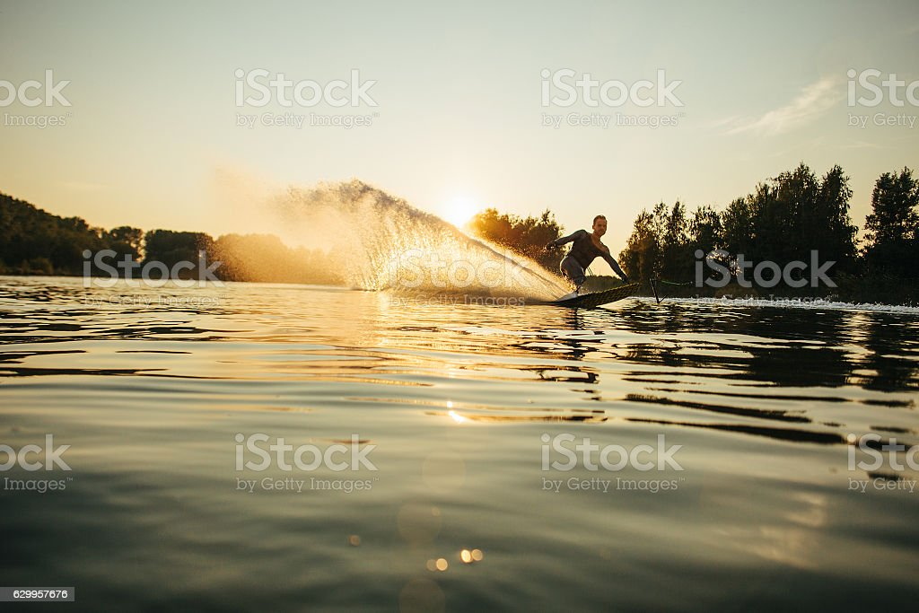 Wakeboarder moving fast in splashes of water stock photo