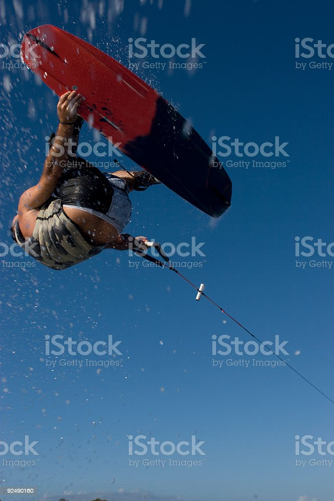 Wakeboarder shot from under flies through the air stock photo