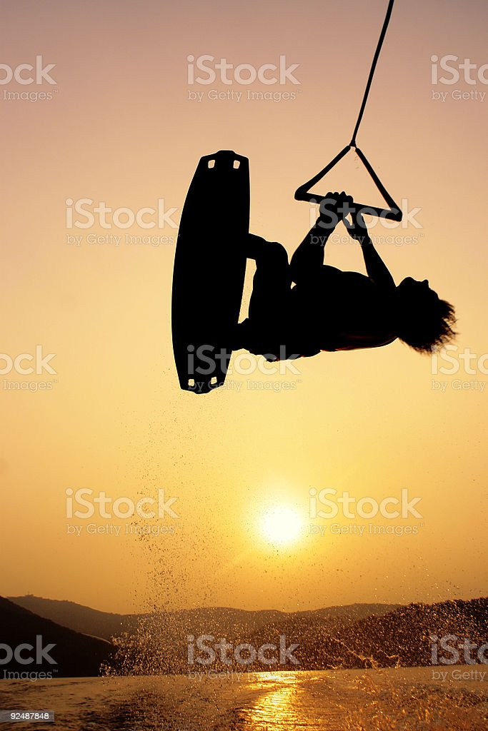 Wakeboarder silhouette on sunset flying in mid air royalty-free stock photo