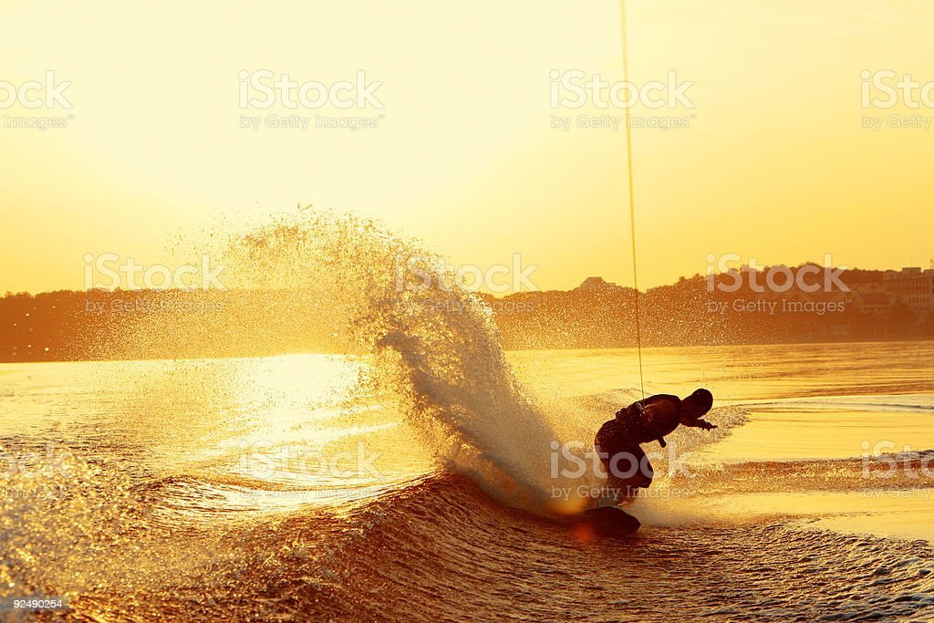 Wakeboarder slashes wake on heel side during sunset stock photo