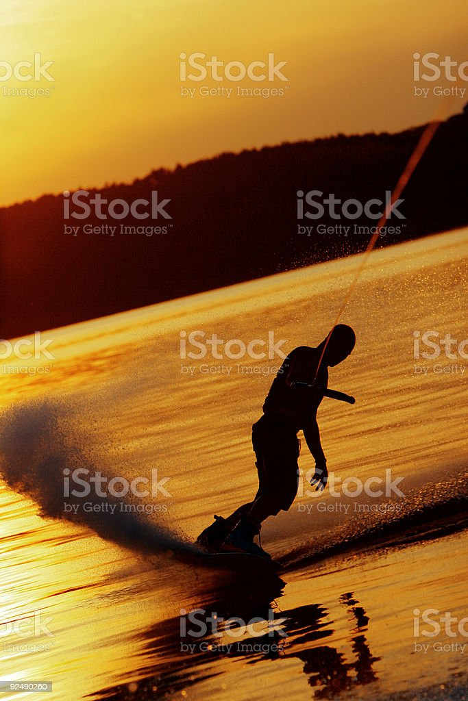 Wakeboarder slides on glassy water at sunset royalty-free stock photo