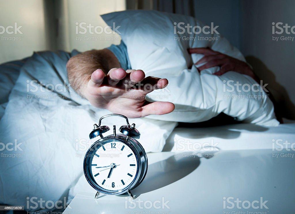Waken man stretching hand to turn off alarm clock stock photo