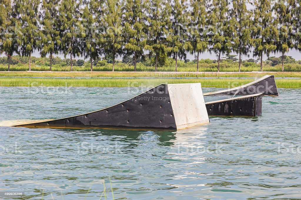 wakeskater slides across a huge floating rail obstacle behind stock photo