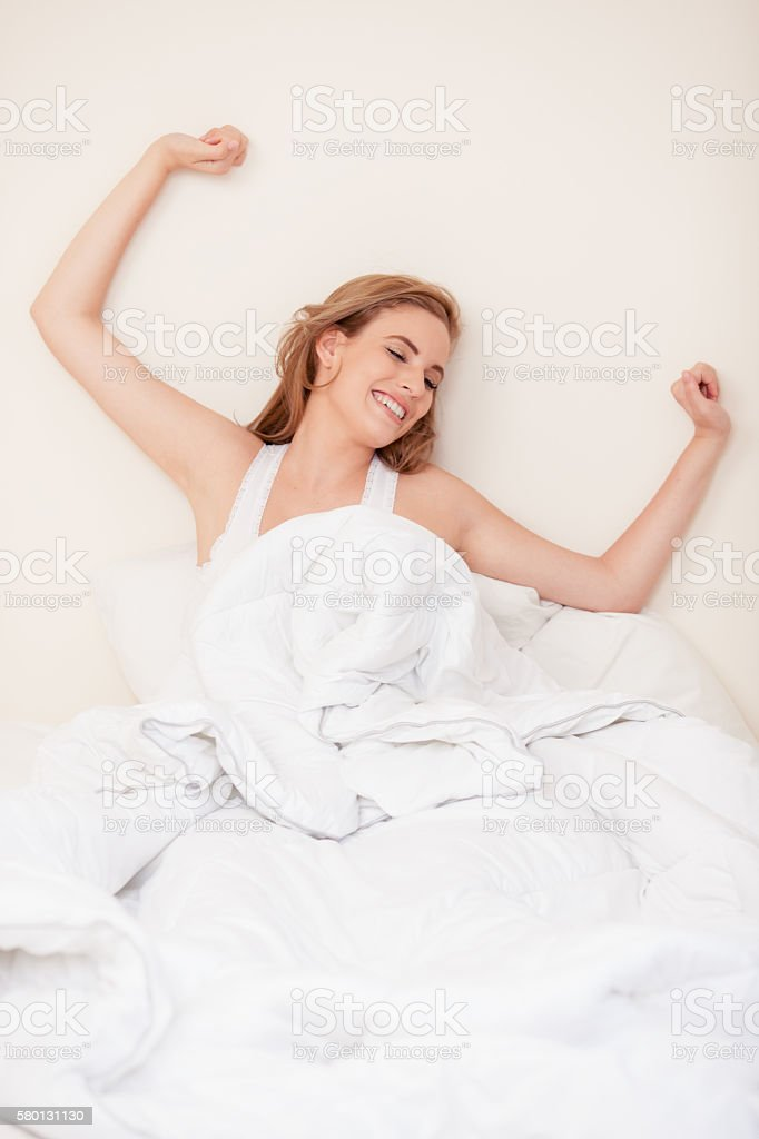 Waking up woman stretching hands. stock photo