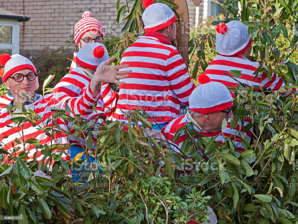 Waldo group trying to hide in a carnival parade UK stock photo