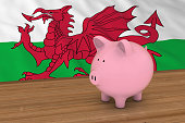 Wales Finance Concept - Piggybank in front of Welsh Flag