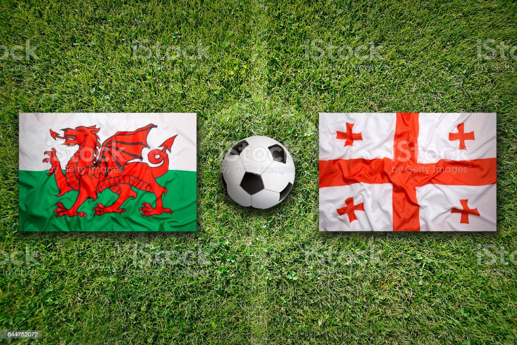 Wales vs. Georgia flags on soccer field stock photo