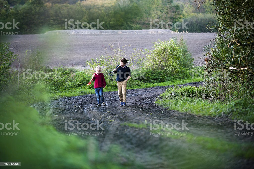 A walk down a country road, shovels in hand.  royalty-free stock photo