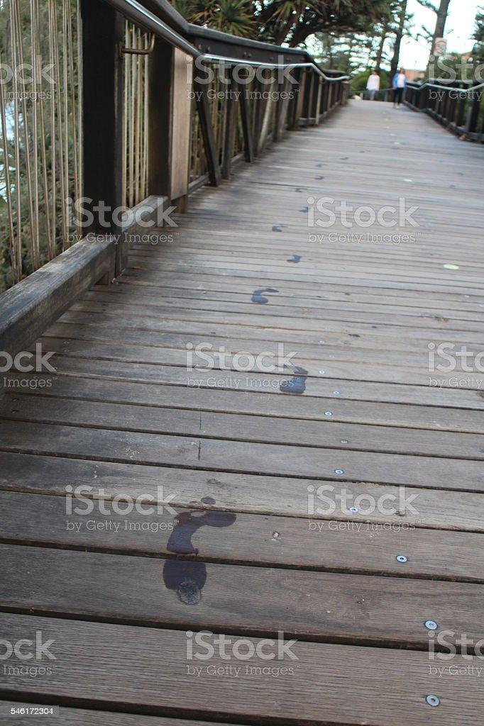 Walk of life; footprints on boardwalk stock photo