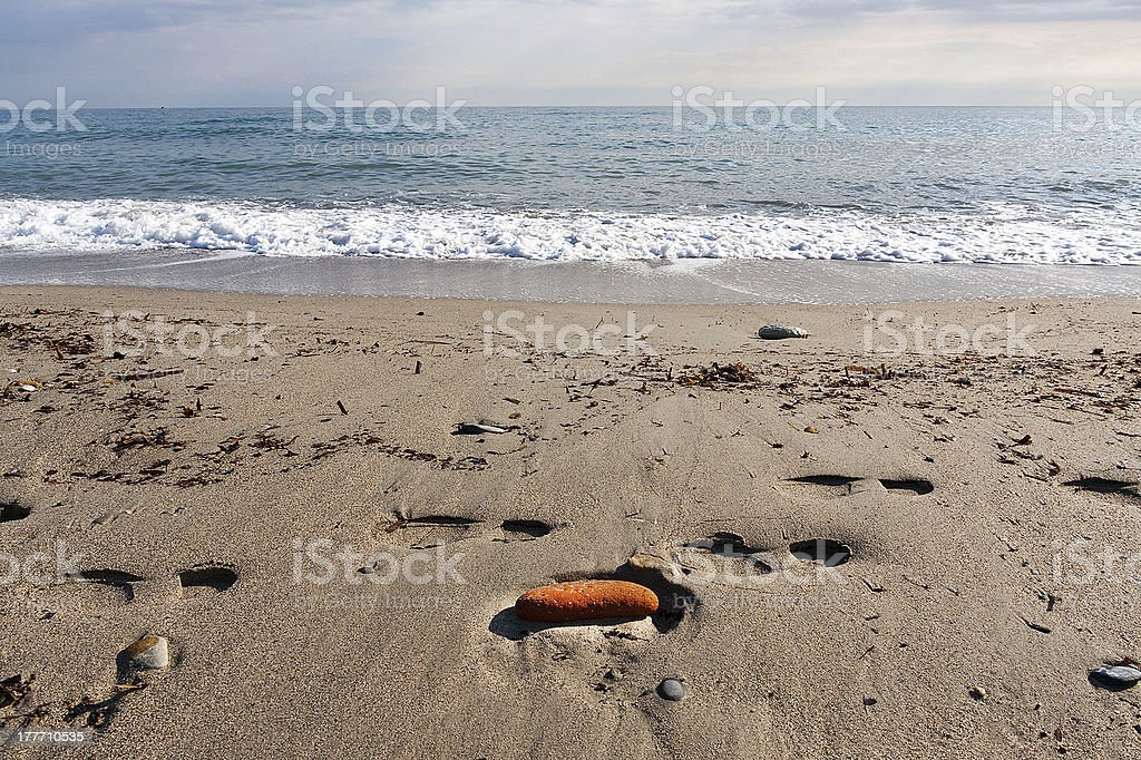 Walk on the beach with footprints and solitary brick royalty-free stock photo