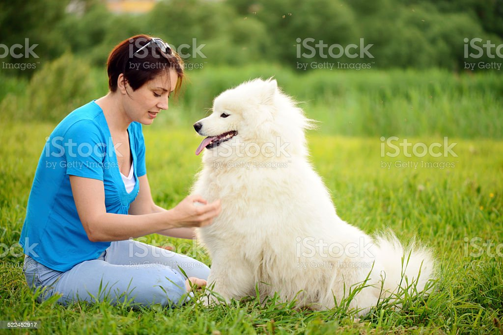 young woman walking with a dog in the summer park.