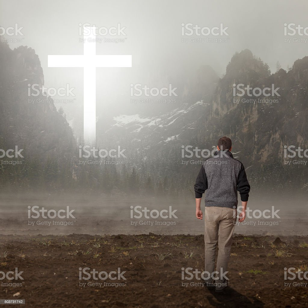 Walk to the cross that appears in the mountain stock photo