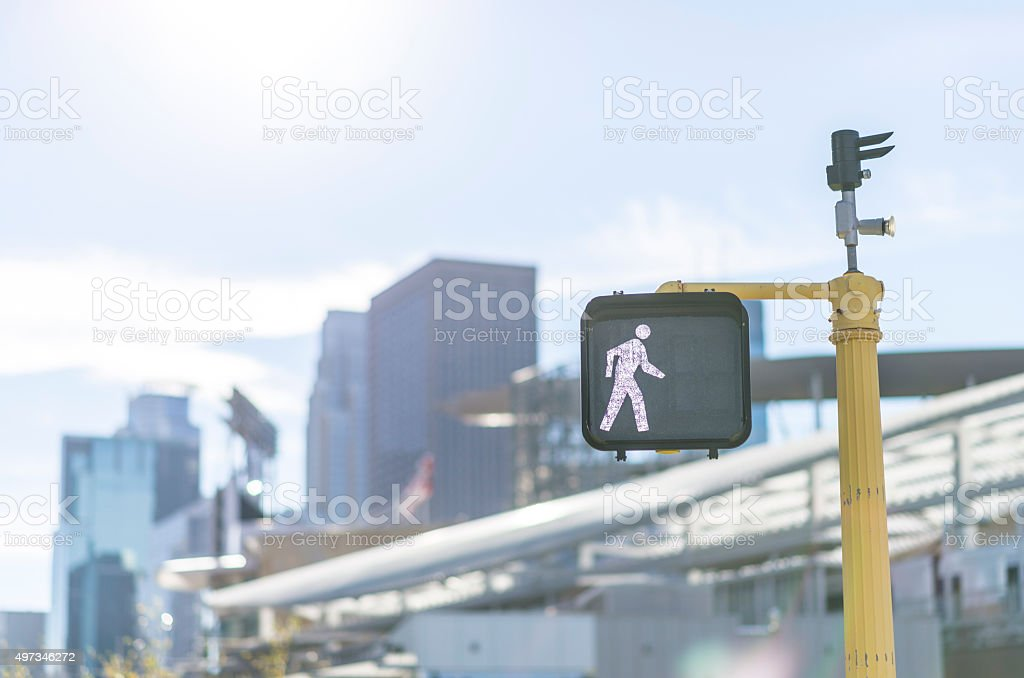 Walk Traffic Signal with City Buildings in Background stock photo