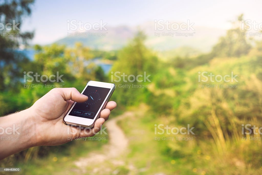 Walker using mobile phone navigation compass - Cumbria / UK stock photo