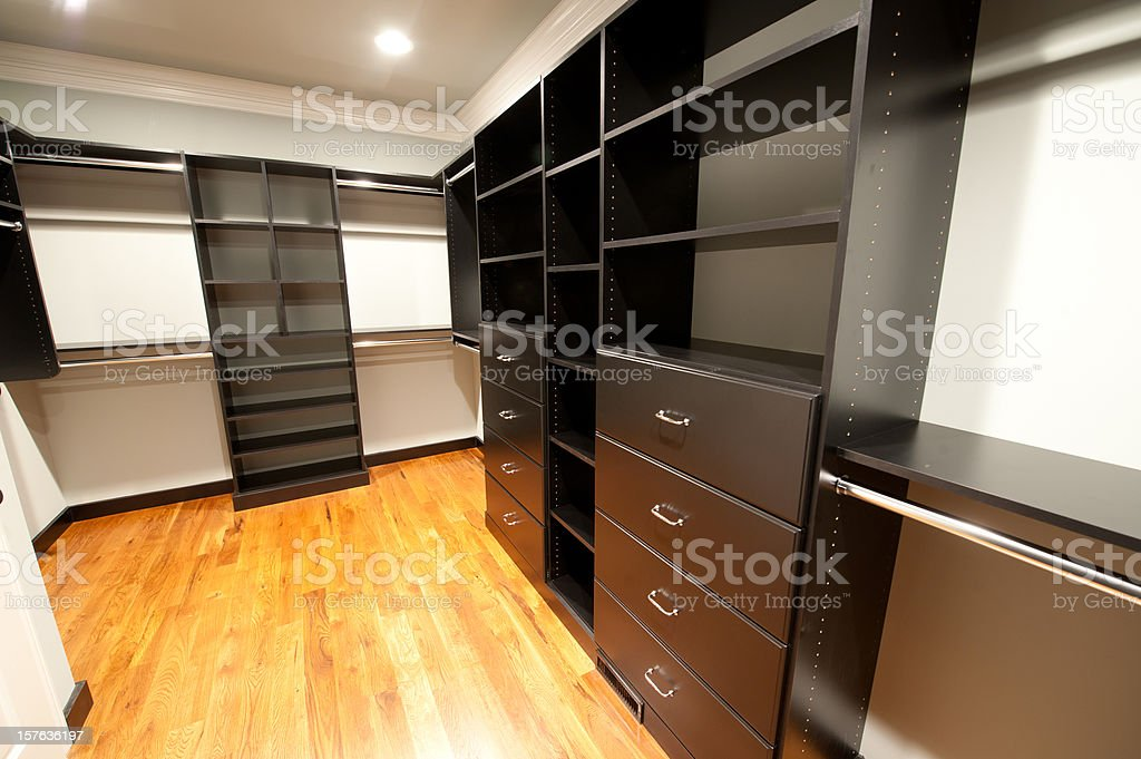 Walk-in closet with black wood paneled cabinets stock photo