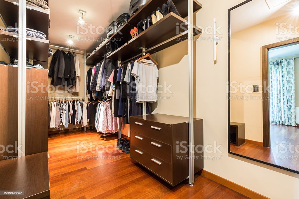 Walk-in closet with wooden wardrobes stock photo