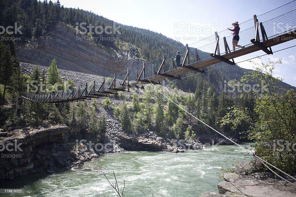 walking across rope bridge stock photo