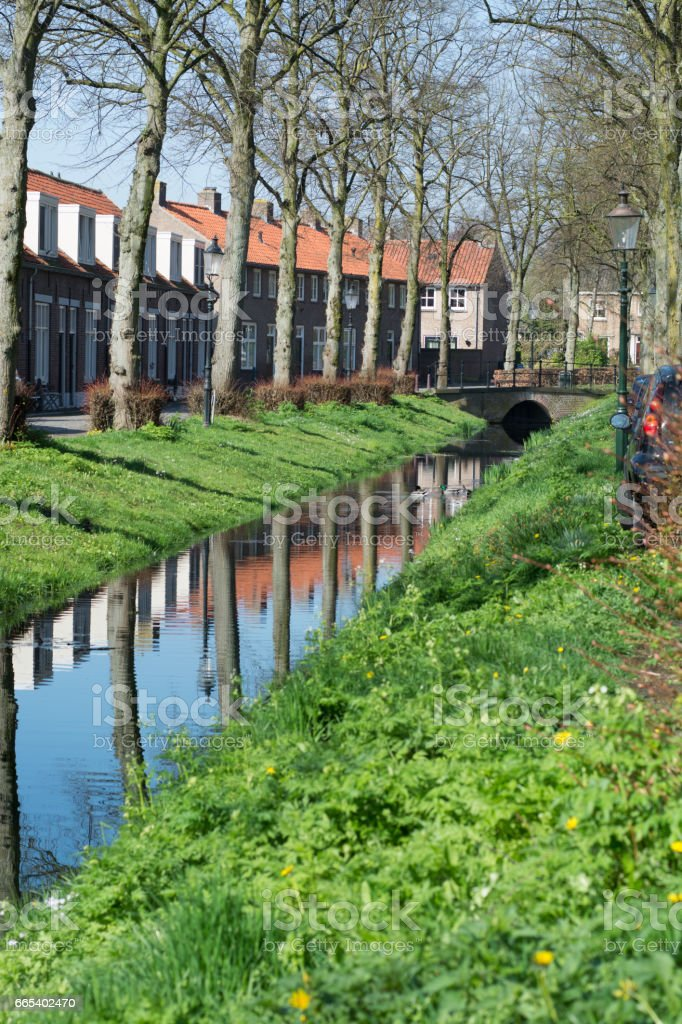 Walking along the small canal in old Dutch village, sunny Sunday morning, reflection in water. stock photo