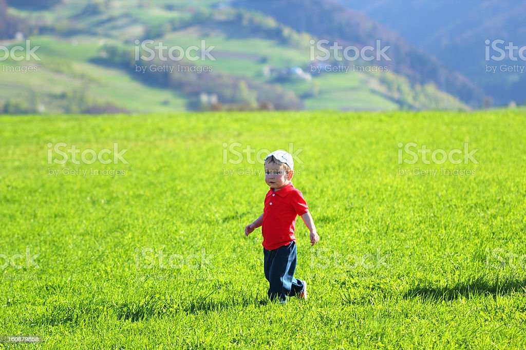 Walking baby boy in mountains on grass background royalty-free stock photo