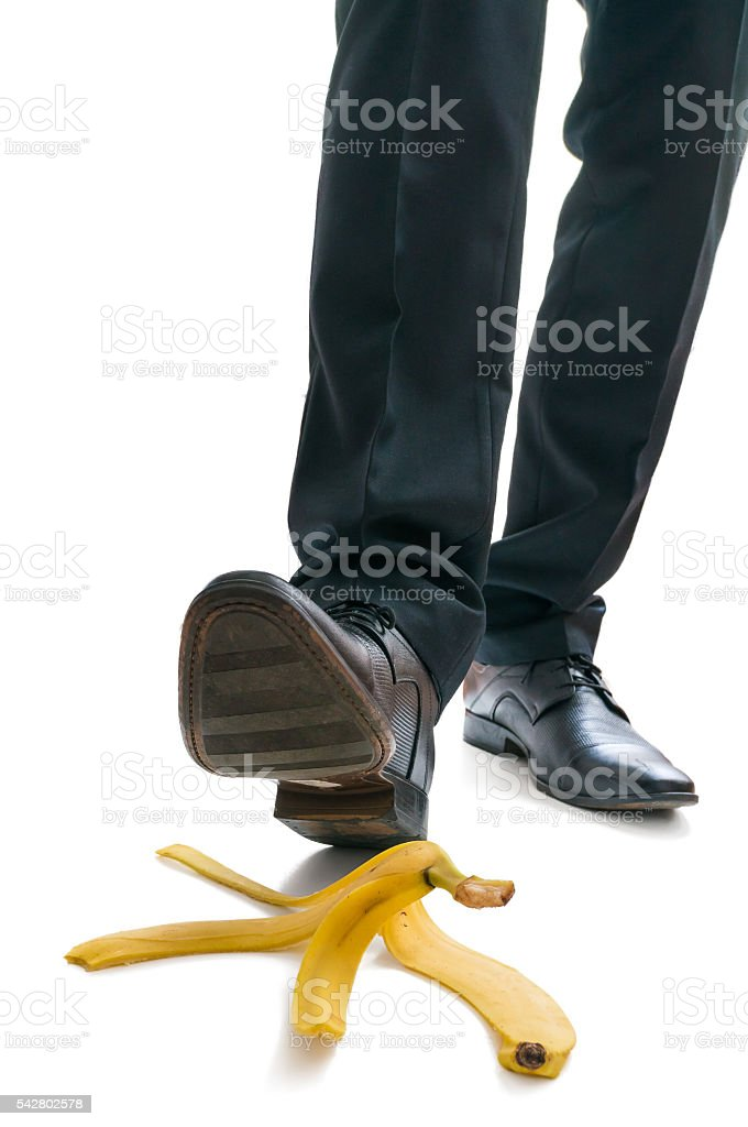 Walking businessman is going to slip on banana peel. stock photo
