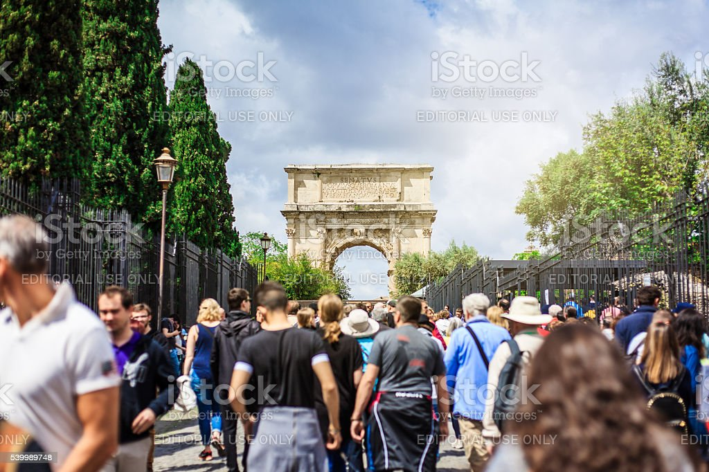 Walking by Roman Forum. Titus Arch in the background. stock photo
