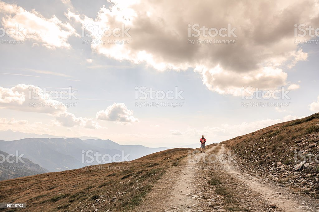 walking in solitude - female hiker before mountains scenery stock photo