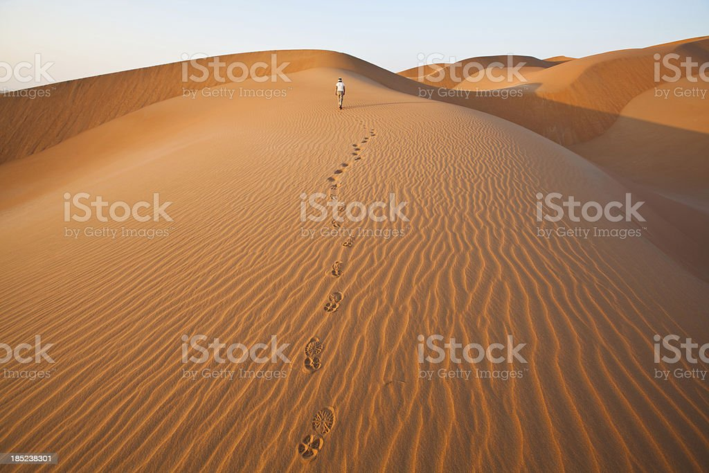 Walking in the sand dunes with foot prints stock photo