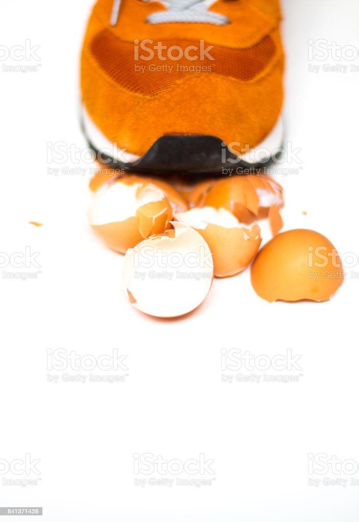 Walking on Eggshells: Orange Shoe and Eggshells (Close-Up) stock photo
