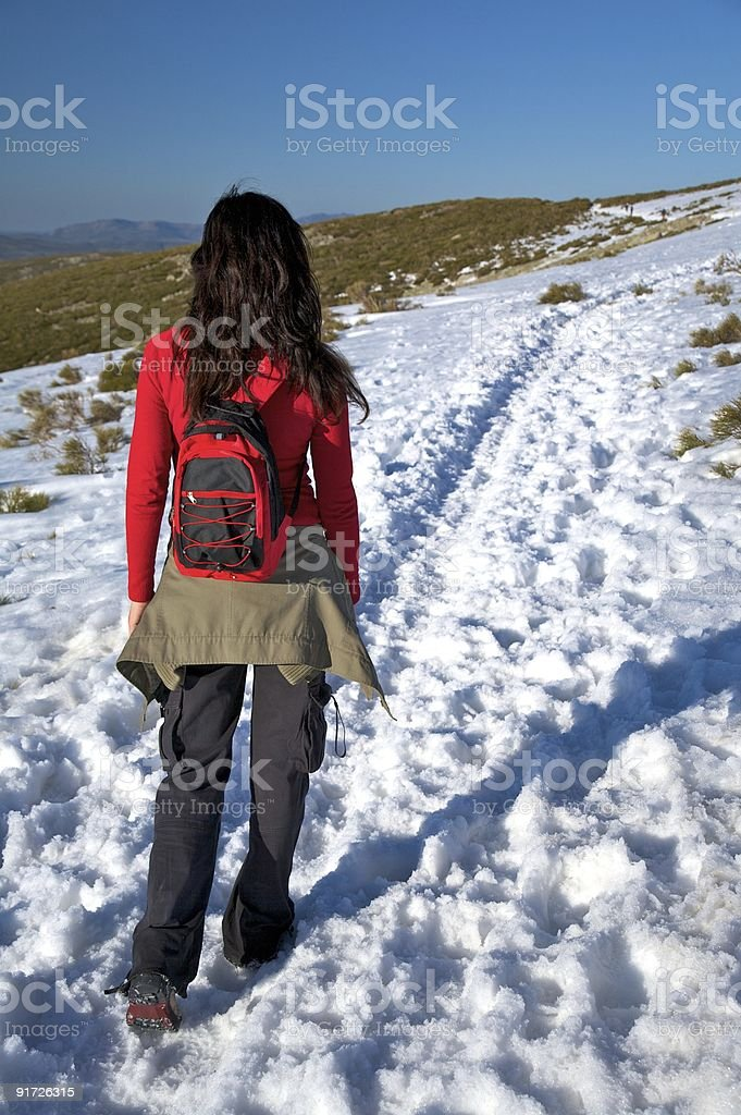 walking on long snow path royalty-free stock photo