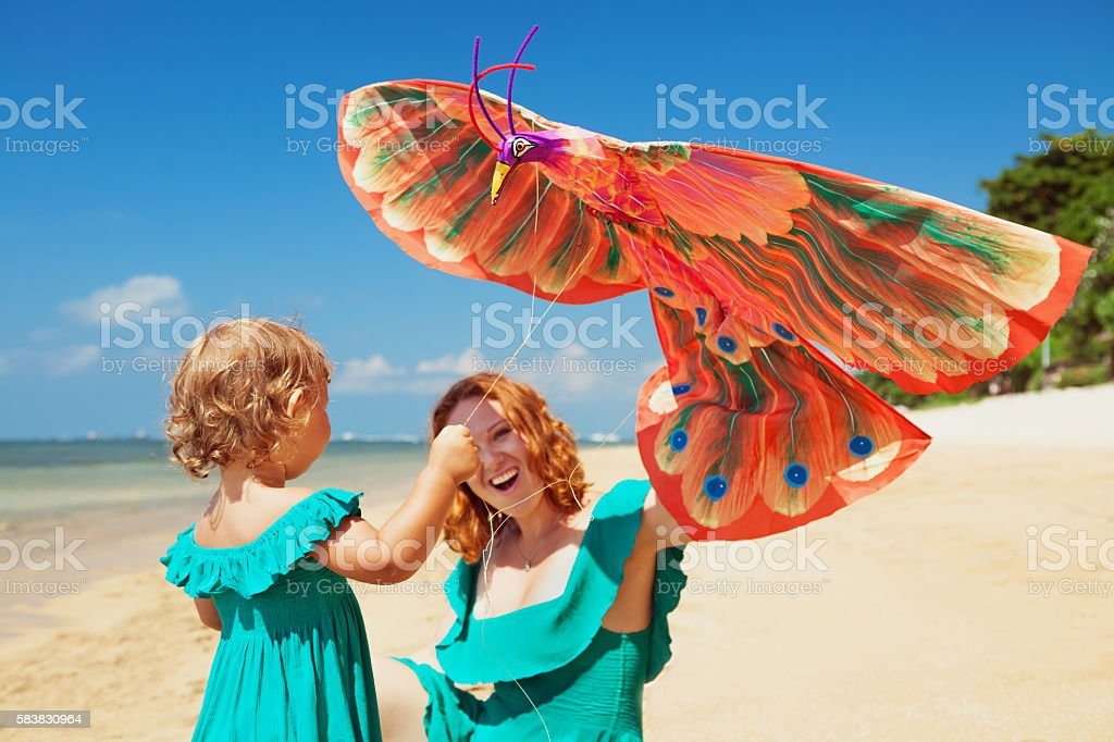Walking on ocean beach mother and child launch kite stock photo