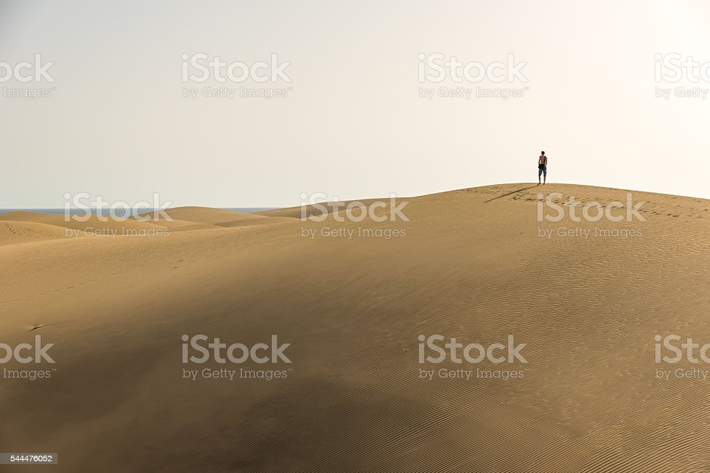 Walking on sand dunes in desert with sunset stock photo