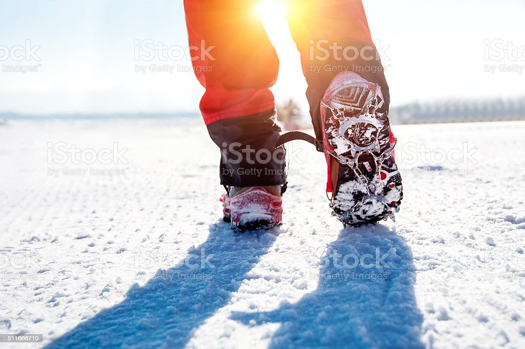 walking on snow with Snow shoes and Shoe spikes. stock photo