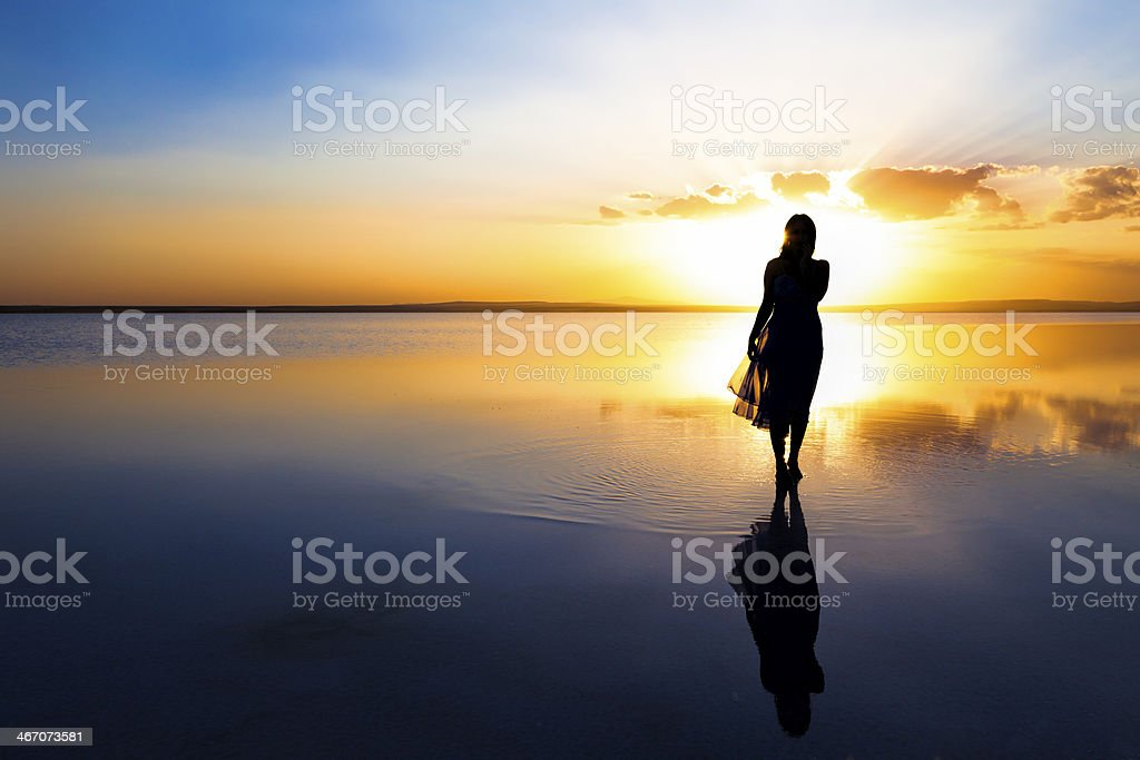 Walking on water at sunset stock photo