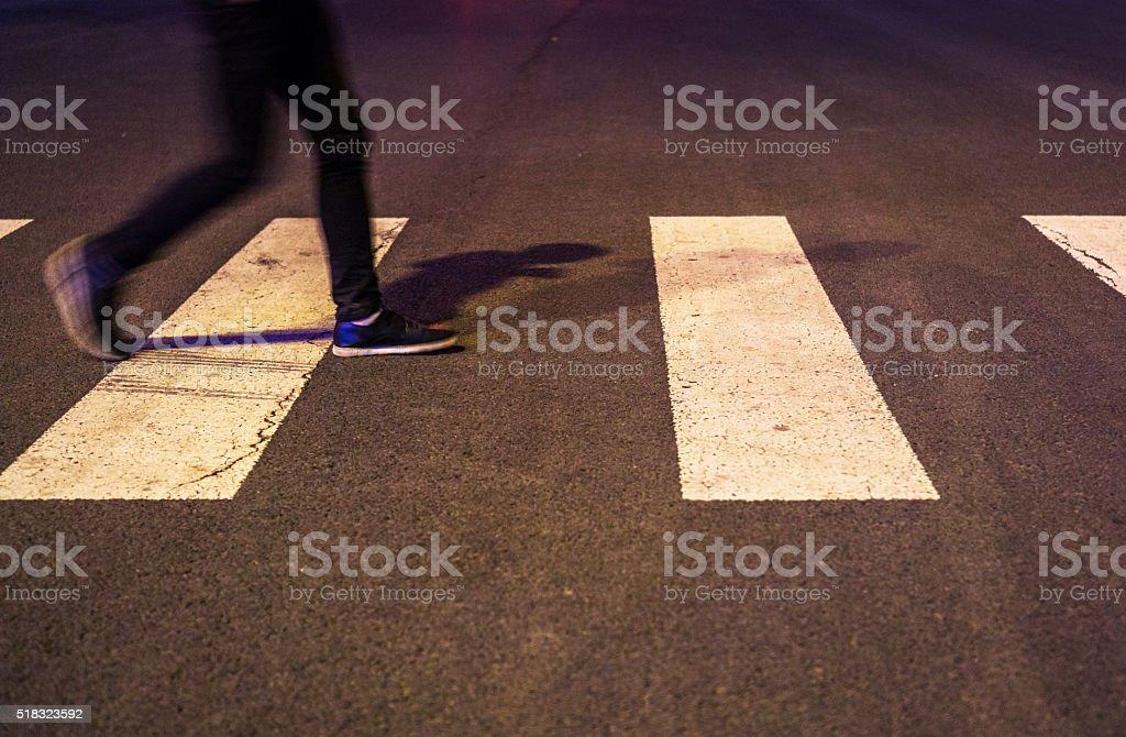 walking on zebra crossing at night stock photo