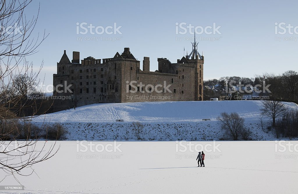 Walking over the frozen loch, Linlithgow Palace, Scotland. stock photo