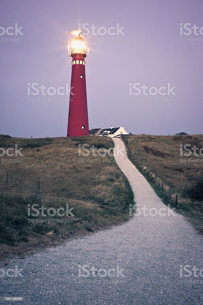 Walking Path Through Fields Towards Lighthouse After Sunset stock photo