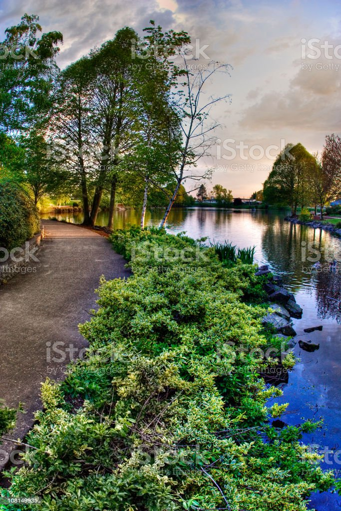 Walking Pathway Along River's Edge and Green Forest royalty-free stock photo