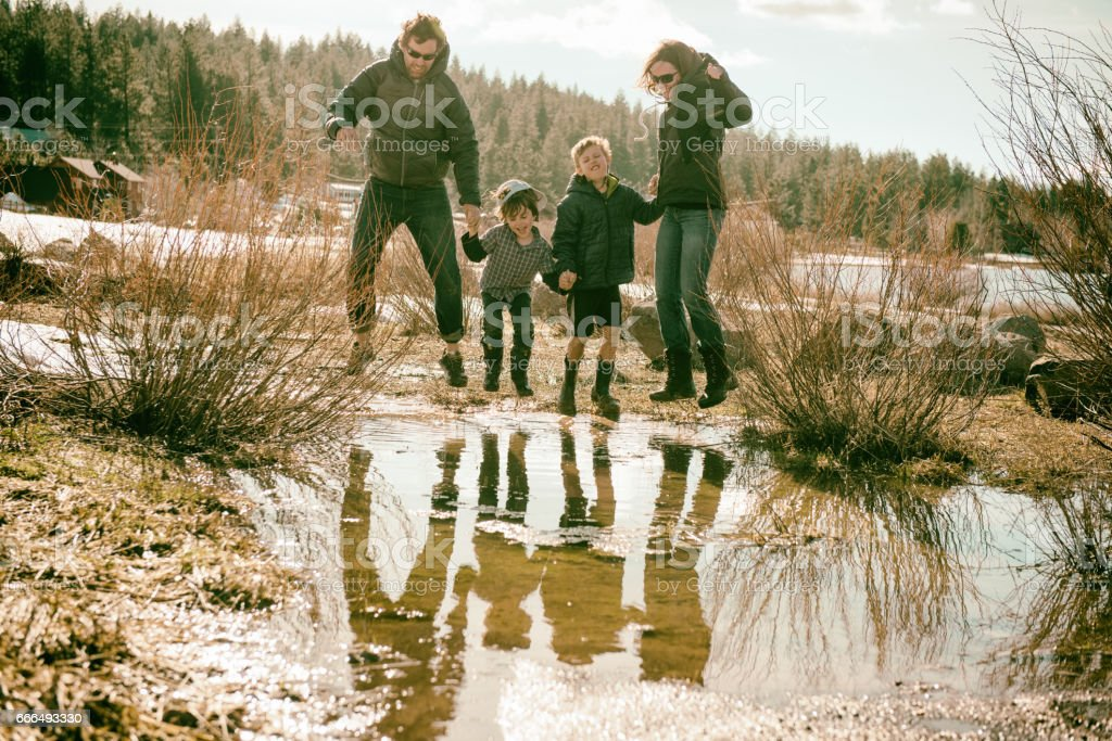 Walking through mud puddles with family stock photo