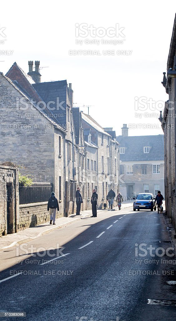 Walking to work along small road in Cirencester stock photo
