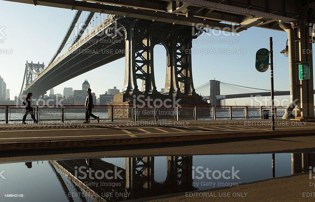 NYC walking to work under Manhattan Bridge puddle reflection stock photo