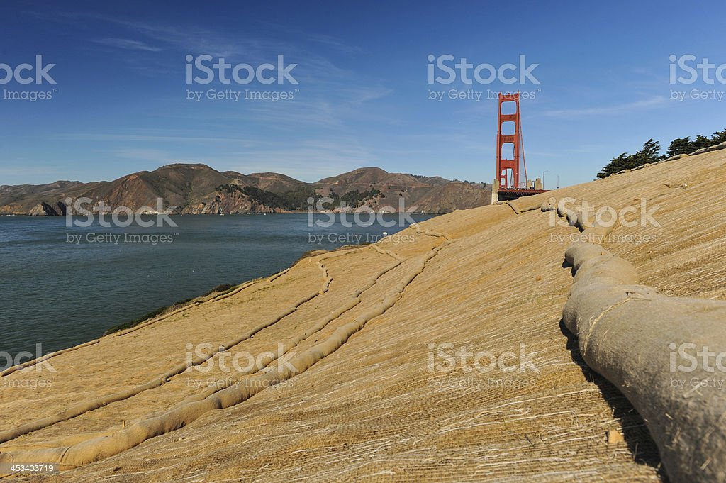 Walking trail next to ocean with erosion control mesh stock photo