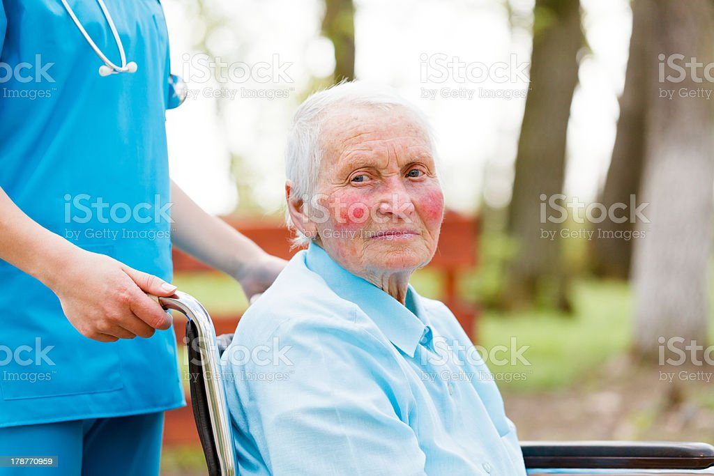 Walking with an Elderly Lady in Wheelchair royalty-free stock photo